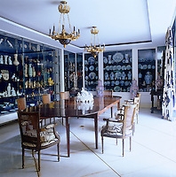 This formal dining room has been lined with glass cabinets housing an impressive collection of china and ceramics