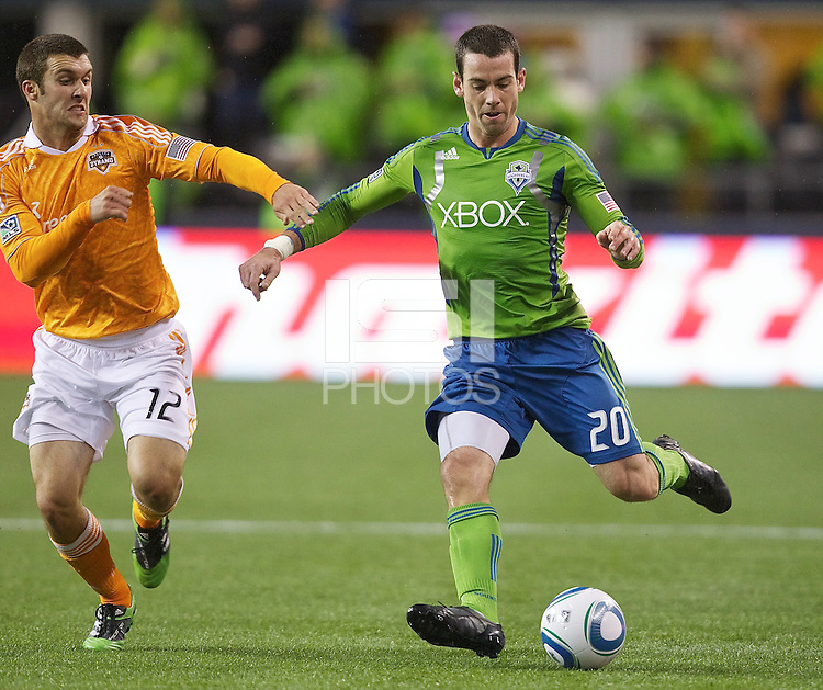 Seattle Sounders FC defender Zach Scott passes the ball in front of Houston Dynamo forward Will Bruin during play at Qwest Field in Seattle Friday March 25, 2011. The match ended in a 1-1 draw.