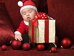 Six month old baby boy in Santa costume sleeping with a Christmas present in his lap