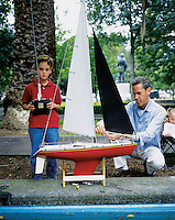 A father and son make final adjustments to their remote controled sail boat before placing it in the water at Parque Lincoln, Polanco, Mexico City, September, 2005