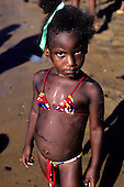 Bahia, Brazil. Young girl, red and colours  bikini, covered in sand from beach, looking defiantly into the camera.