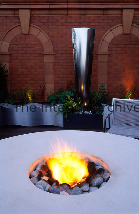 Lit flambe' with benches, chair and water feature beyond at dusk