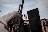 In this Thursday, Sep. 19, 2013 photo, a Syrian young girl walks on the roof of a house as opposition fighters prepare themselves for the combat in a neighbouring village of Kafr Nabuda in the Idlib province countryside, Syria. (Photo/AP).