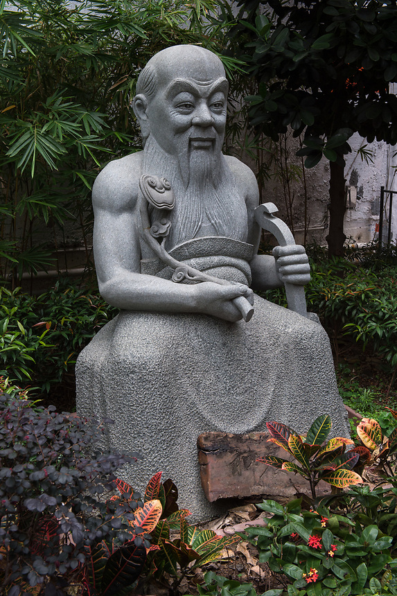 "HONG KONG SAR: CHINA - March 07 ,2018: Statue of Shennong in the Queen Street Rest Garden Bonham Street Sheung Wan.The garden has over 100 plants used in Chinese medicine on display with explanation of their uses. Shennong, translated as ""God farmer"", is credited as the Father of Chinese medicine."