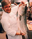 USA, California, Los Angeles, portrait of Chef Michael Cimarusti holding a fish in the kitchen of his restaurant Providence.