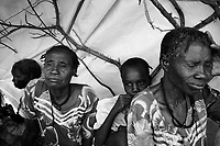 Beredjing refugee camp, Tchad, June 14, 2004.A family of new arrivals tries to protect themselves from the blazing sun under a sheet of plastic. In less then 2 weeks this camp's population has swollen from 600 to 13000, an average of 1000 new arrivals show up every day...