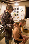 Young man shaving his brother's head home haircut in kitchen, UK - model released