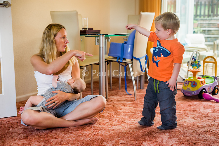 A woman sitting crossed-legged at home on her living room carpet, pointing and talking to her toddler son and  breastfeeding her baby.<br /> <br /> 09/07/2011<br /> Hampshire, England, UK