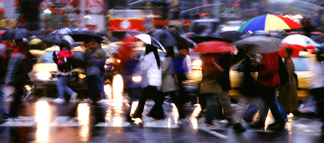Pedestrians with umbrellas cross the street in Times Square, New York City, USA in the rain
