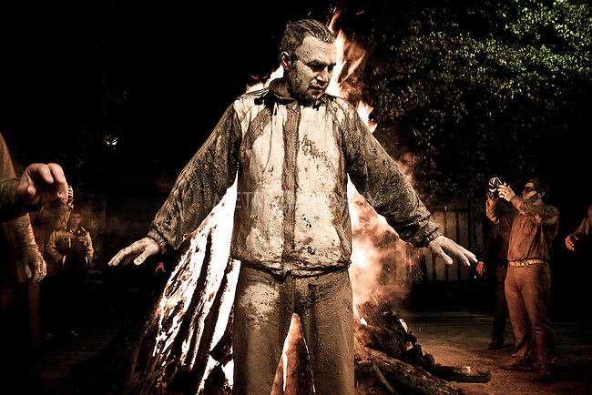 KHORRAMABAD, IRAN : A man dries his muddy body next to a fire during the festival of Ashura...Every year to mark the death of Imam Hussein, Shia Muslims mourn for two days. In Khorramabad and Lorestan in the west of Iran, during the first day of mourning, called Tasooa, women take a vow of silence and go through the streets with the children lighting candles. At 4 am on Ashura, the second day, men cover themselves in mud and then stand in front of a fire until the mud has dried to clay. After this they go to the mosque and pray...Photo by Farhad Babaei/Metrography