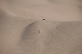 Ica, Peru. La Huacachina, an oasis and resort area just outside of Ica, Peru. Visitor at resort climbs sand dunes on the site. No MR. ID: AL-peru.