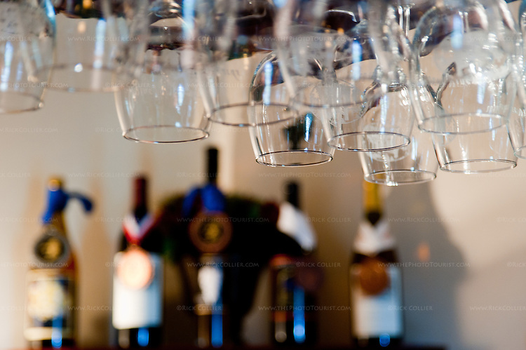 The tasting bar at Old House Vineyards is framed by glasses above and bottles with awards all around.