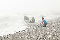 A female tramper watching waves at Three Mile Beach near Okarito - Westland National Park, West Coast, New Zealand