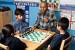 Afterschool chess program for elementary students graduates of Headstart program male teacher working with two boys and a girl