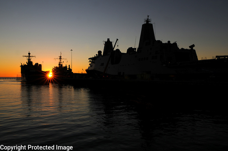 The sun sets in the Pacific Ocean behind the U.S.S. Pearl Harbor, left, the    Comphibron, center, and the U.S.S. Green Bay, right, on Jan. 10, 2009 at the Naval Base San Diego in San Diego, California.