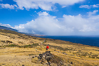 A man in a red jacket stands on a rocky outcrop in Kaupo along Piilani Highway, Maui.