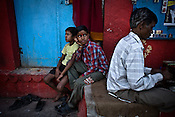 Young boys site next to a pan shop on the ghats of Benares, Uttar Pradesh, India.