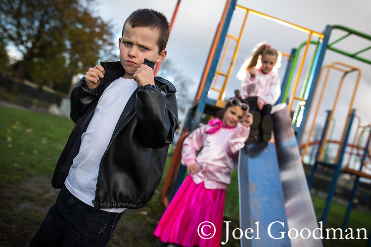 © Joel Goodman - 07973 332324 . 7th November 2013 . Godfrey Ermen C of E Primary School , School Road , Eccles , M30 7BJ , UK . L-R Rorie Whitehead (six , from Eccles) , Molly Hall (six , from Warrington) and Millie Sandlan (six from Peel Green) (all correct) in 1950s garb , as if out of Greese . Children come to school dressed up in the fashions of the past 110 years to celebrate the school's 110th birthday . Photo credit : Joel Goodman