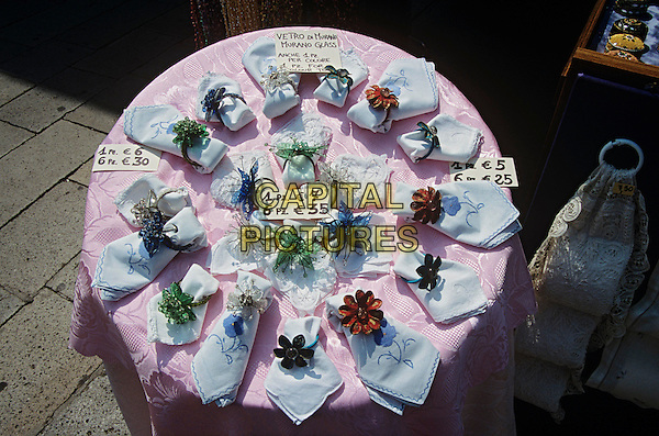 Murano glass napkin rings and napkins for sale on display outside shop, Burano, Venice, Italy