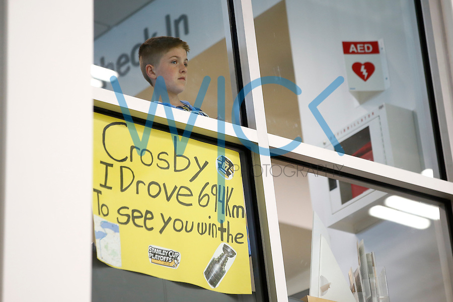 A young fan looks on with his sign from above the Pittsburgh Penguins practice at UPMC Lemieux Sports Complex in Cranberry Township, Pennsylvania on June 8, 2016. (Photo by Jared Wickerham / DKPS)