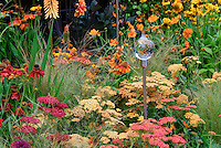 Achilea, Helenium, Kniphofia, Dahlia, ornamental grass, glass garden ornament for sunset hot warm toned color theme garden of orange, yellow, reds perennials flowers, glass flower