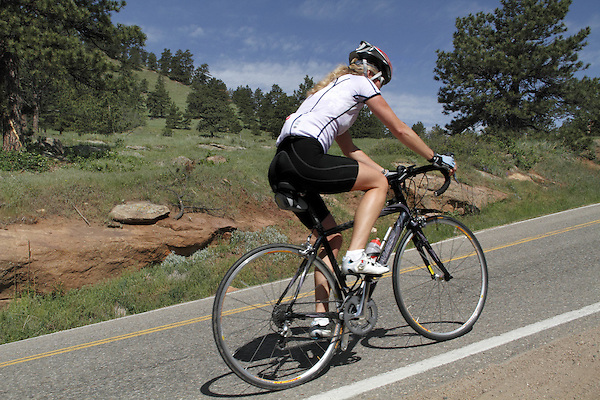 Female biking uphill on Flagstaff Mountain Road west of Boulder, Colorado. .  John leads private photo tours in Boulder and throughout Colorado. Year-round.