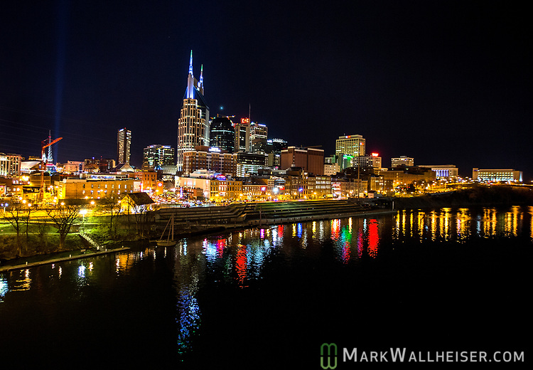 The nighttime skyline of Nashville, Tennessee over the Cumberland River.