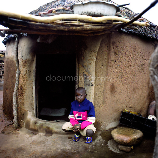 A little boy in front of his hut.