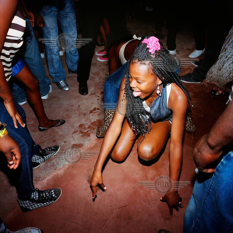 A young girl dancing to Kuduru/Kuduro music at disco. .