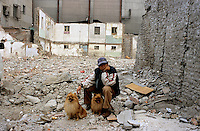 CHINA. Beijing. A man and his dogs sit amongst the ruins of an old hutong (tradtional home) destroyed to make may for new developments aimed at modernising the city for the 2008 Summer Olympics. 2005