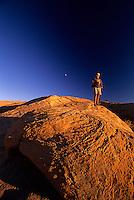 Golden light of sunset shining on man standing on featured sandstone hill, Moab, Utah