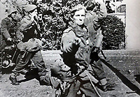 BNPS.co.uk (01202 558833)<br /> Pic: JackReynolds/BNPS<br /> <br /> Jack spots the smiling German cameraman after being taken prisoner at Arnhem.<br /> <br /> A war hero who famously photographed flicking a V-sign at his German captors after being taken prisoner at Battle of Arnhem 75 years ago has died.<br /> <br /> Liuetenant Jack Reynold's plucky act of defiance towards his captors provided one of the most iconic images to come out of doomed Operation Market Garden.<br /> <br /> The officer and his men were overrun by the Germans three days after 10,000 British airborne troops landed behind enemy lines in Holland in the audacious operation.<br /> <br /> As they were being marched away Lt Reynolds spotted a grinning German cameraman shooting video of the vanquished Brits.