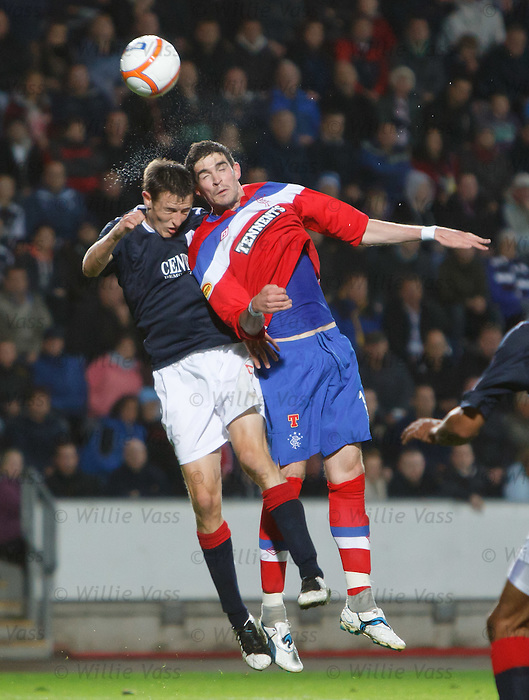 Kyle Lafferty takes a sore one to the head from Murray Wallace as they clash in the air