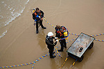 Looking down from above at professional divers on a beach about to enter the sea to work on the pier at Cromer, north Norfolk coast, England