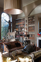 The collection of anthropological artefacts and taxidermy are literally piled on top of each other on pieces of furniture and mounted on the walls of the library