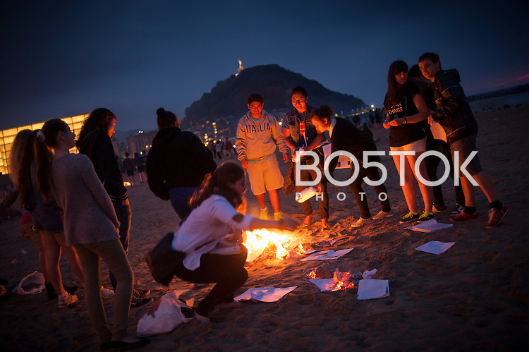 A group of teenagers plays around a bonfire. Donostia - San Sebastian (Basque Country) June 23, 2014.  As every where around the world, in the Basque Country people welcomes the summer around a bonfire. (Gari Garaialde / BostokPhoto)
