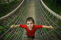 Young boy in red shirt plays on rope bridge in park.