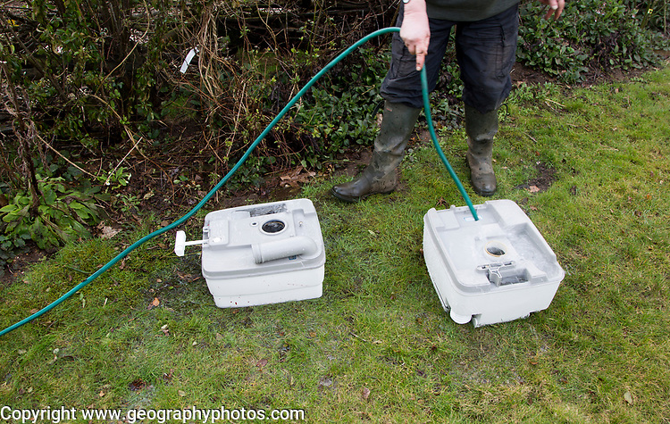 Woman using garden hose water pipe to wash clean camping toilet container cartridge, UK