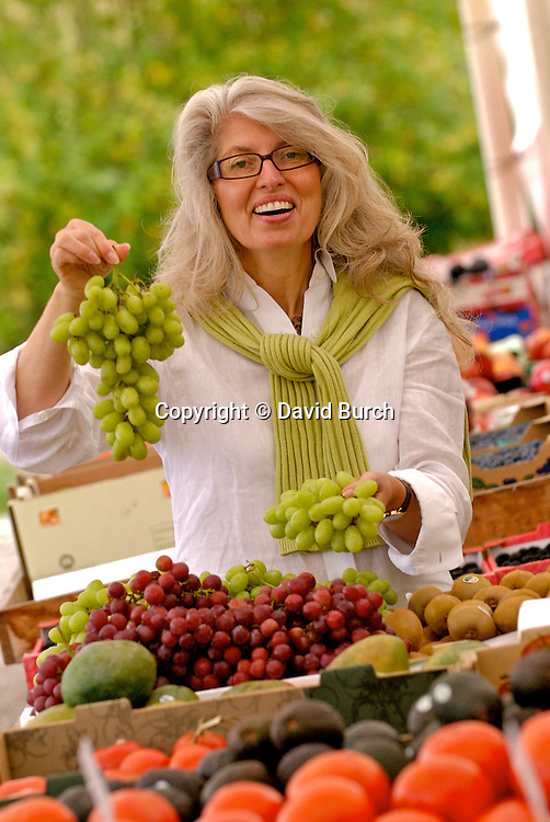 Mature woman holding bunch of grapes, smiling