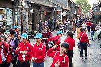 Yangzhou, Jiangsu, China.  Dong Guan Street Scene, Chinese Schoolchildren in Foreground.