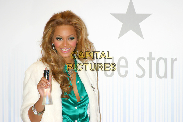 BEYONCE KNOWLES .At The True Star Perfume Launch Held At Macy's, Herald Square, New York City..October 22nd, 2004.half length, green silk, satin blouse, white fur coat, brooch, bottle.www.capitalpictures.com.sales@capitalpictures.com.©Capital PIctures