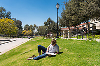 Jack Brancheau '18 reads his economics book<br /> near Gilman Fountain, March 28, 2018.<br /> (Photo by Marc Campos, Occidental College Photographer)