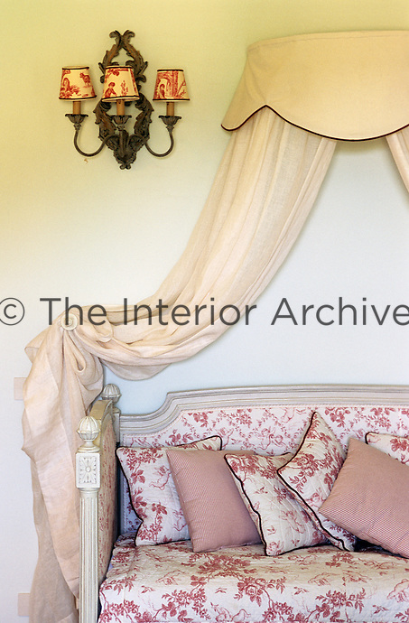 This elegant day bed is decorated with a wall mounted canopy and matching cushions