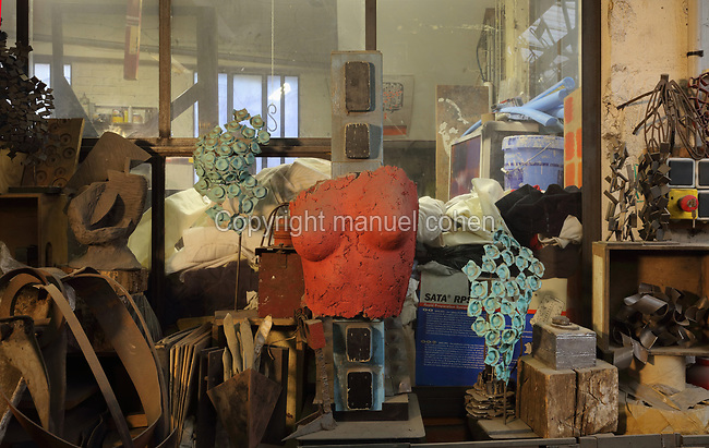 Clay mould for a figurative sculpture and various raw materials and prototypes on a shelf in the Soleil Rouge workshop of Nicolas Desbons, metalworker and artist, photographed in 2017, in Montreuil, a suburb of Paris, France. Desbons works mainly in steel but often in conjunction with other materials such as fibreglass, glass and clay, using both cold metal and forge techniques. He produces both figurative and abstract sculptures as well as furniture and lighting. Picture by Manuel Cohen