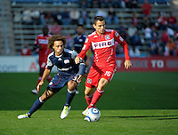 Chicago midfielder Marco Pappa (16) looks to keep the ball away from New England defender Kevin Alston (30).  The Chicago Fire defeated the New England Revolution 3-2 at Toyota Park in Bridgeview, IL on Sept. 25, 2011.