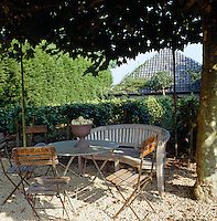 In the centre of the vineyard a simple round table, wooden bench and chairs sit in the shade of trees