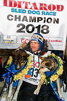 Joar Leifseth Ulsom poses with his lead dogs Russeren (left) and Olive on the winner's podium at the finish line in Nome, Alaska early on Wednesday morning March 14th as he wins the 46th running of the 2018 Iditarod Sled Dog Race.  He finished in 9 days 12 hours 00 minutes and 00 seconds<br /> <br /> Photo by Jeff Schultz/SchultzPhoto.com  (C) 2018  ALL RIGHTS RESERVED