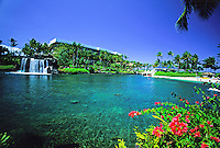The serene rock waterfall, blue lagoon, white sand beach, and clear blue skies are a vacationer's paradise at the Hilton Waikaloa Village on the Big Island of Hawaii.