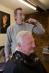 With newly shorn hair on his shoulders, a customer, Ken, smirks as Mike an amusing anecdote involving the portrait on the wall.