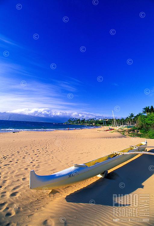 Outrigger canoe on sand on Kapalua beach with deep blue sky
